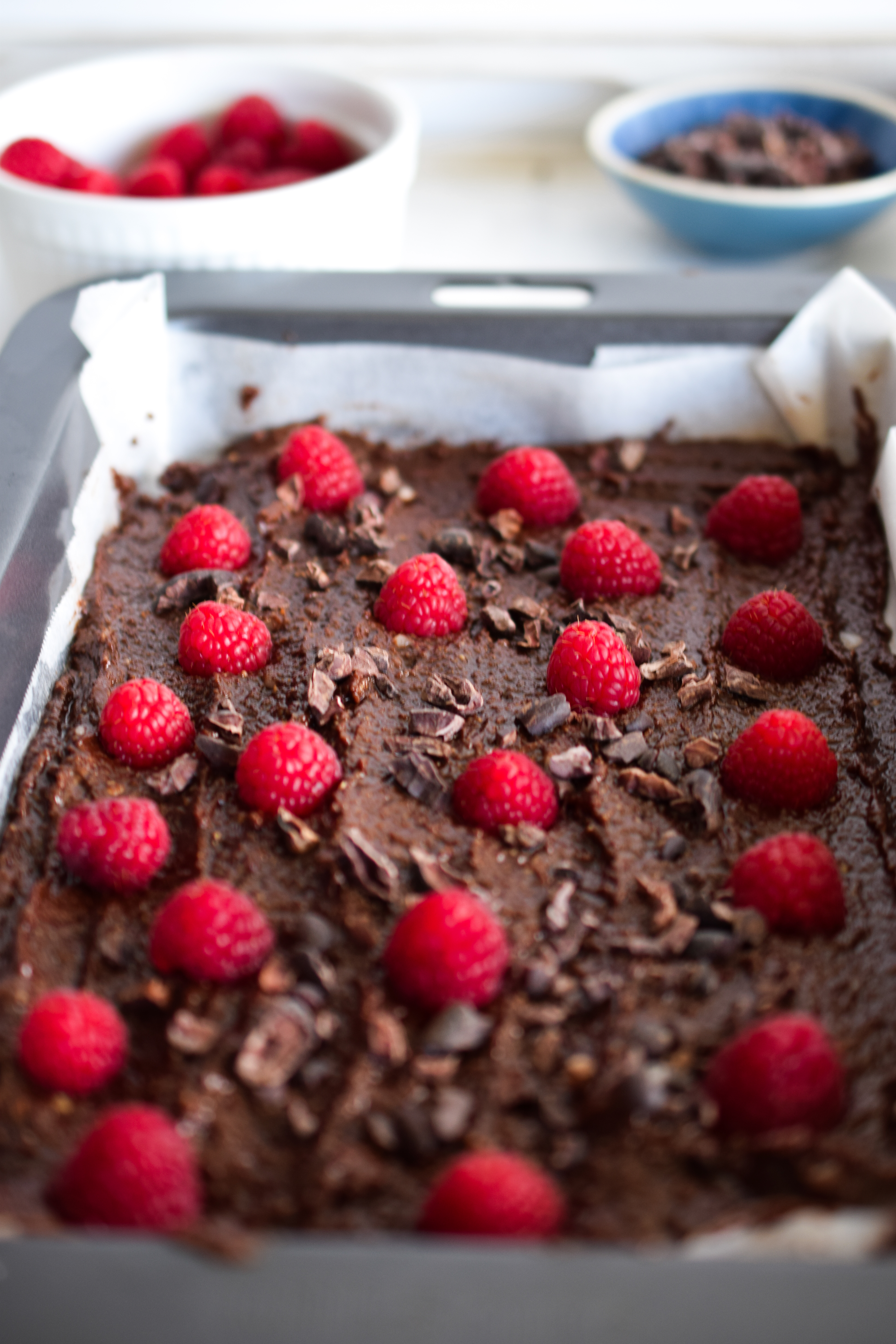 Chocolate Raspberry Fudge with bowl of fresh raspberries and bowl of cacao nibs